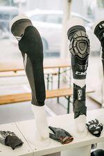 """Rechts im Bild zwei alte Bekannte: der Joint Knee Sleeve von TSG mit segmentierter Polsterung für maximale Beweglichkeit und gleich darunter die """"Ankle Support""""-Bandage mit 3D-Mesh-Gewebe für größtmöglichen Tragekomfort. Daneben haben wir den Prototypen für den Dermis Pro, TSGs neuer kombinierter Knie- und Schienbeinschoner, der """"gap free"""" ist, also keine Unterbrechung zwischen Knie und Schienbein hat. Der Dermis pro ist super dünn und dadurch easy unter der Hose zu tragen. Für die Polsterung kommt der sogenannte viskoelastisch Arti-Lage-Schaum zum Einsatz, der superweich zu tragen ist und sich beim Impact verhärtet. Hört sich interessant an? Dann solltest du Ende Juli mal im BMX-Fachhandel danach fragen, bis dahin sollte der Schoner nämlich bereits erhältlich sein"""