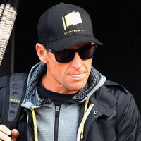 Retired cyclist, Lance Armstrong, wearing a black jacket, baseball cap, and dark sunglasses
