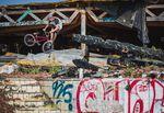 """2018 – Markus """"Maggi"""" Lange –Berlin: Die Wege von Maggi und mir kreuzten sich auf einem kleinen Jam in Berlin und nach kurzem Socialmedia-hin-und-her-Geschreibe verabredete man sich im ehemaligen Spaßbad """" Blubb"""" in Neukölln. Diese Ruine existiert schon seit knapp einem Jahrzehnt. Ich kann mich daran erinnern, dass ich dort mal vor Jahren mit Christian Ramin Fotos gemacht hab und dachte, dass der Spot noch halbwegs fahrbar war … Denkste! Die Hütte wurde x-mal angezündet, ist in sich zusammengestürzt und durch Vandalismus mehr als nur """"verwüstet"""". Wie Maggi da trotzdem noch Tricks ballern konnte, ist mir bis heute ein Rätsel, denn selbst der Weg über das Gelände war schon ein reines Survival-Abenteuer … Aber das Foto ist der Beweis: Radkontrolle at its best!"""