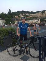 Jonas Deichmann in Frankreich. Im Hintergrund kann man eines der vielen Tour-de-France-Spektakel entlang der Strecke sehen.