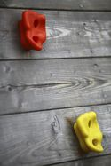 A red and yellow climbing hold on a grey wooden wall