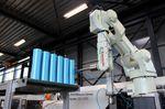Hier entfernt der Roboter Kunststoffreste von den Rollenzylindern. Erst wenn alle Rückstände beseitigt sind kann es mit dem nächsten Schritt der Produktion weitergehen.