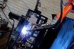 Auf der einen Seite befestigt ein Mitarbeiter einen Rahmen in einer dafür vorgesehenen Halterung und auf der anderen Seite schweißt der Roboter. Im Anschluss werden die Seiten gewechselt. Der Mitarbeiter prüft den fertigen Rahmen und der Roboter schweißt den Nächsten.