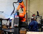Ein Tacx-Mitarbeiter und der abgebildete Roboter arbeiten zusammen, um den Rahmen eines Heimtrainers zu verschweißen.
