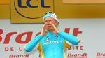The cyclist, Alexandre Vinokourov, wearing the light blue and yellow kit of Astana, cups his hands around his mouth while stood on the Tour de France podium